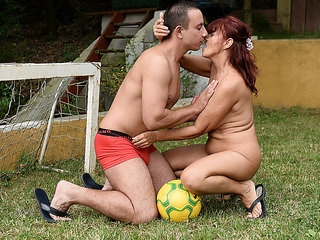 Aged redhead is having outdoor sex with a younger boy
